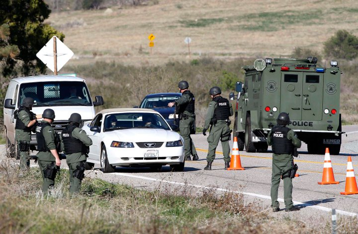 Armed police officers search vehicles driving south in Yucaipa during the manhunt for fugitive former Los Angeles police officer Dorner