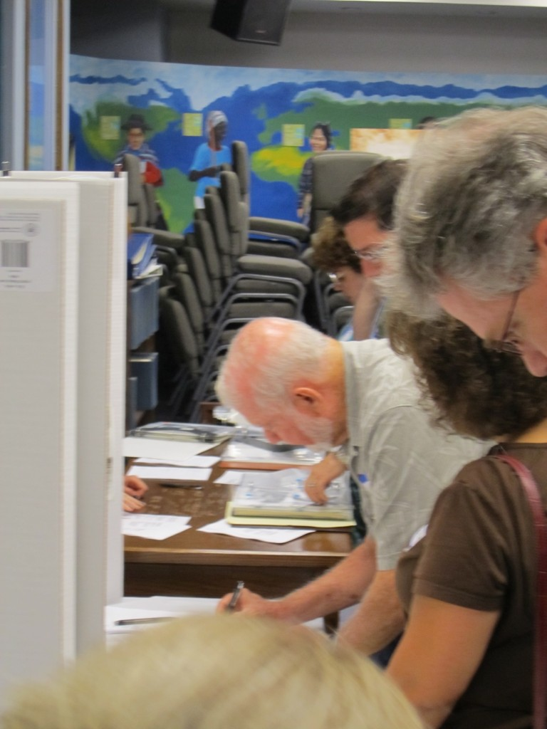 People filling out metadata forms infront of a photo display.